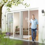 Man walking out of a sliding terrace door with installed insect screens.