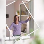 Woman demonstrating the loading frame inside a window.